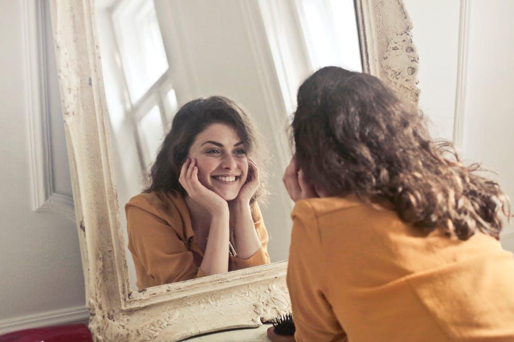(出門前對著鏡子裡的自己笑一下 / 圖:Pexels)